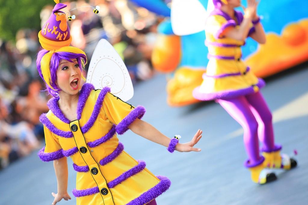 """""""ハニービー"""" プーたちのフロートの前で飛び回るハチをイメージしたダンサー。ティガーとも仲良しの様子"""