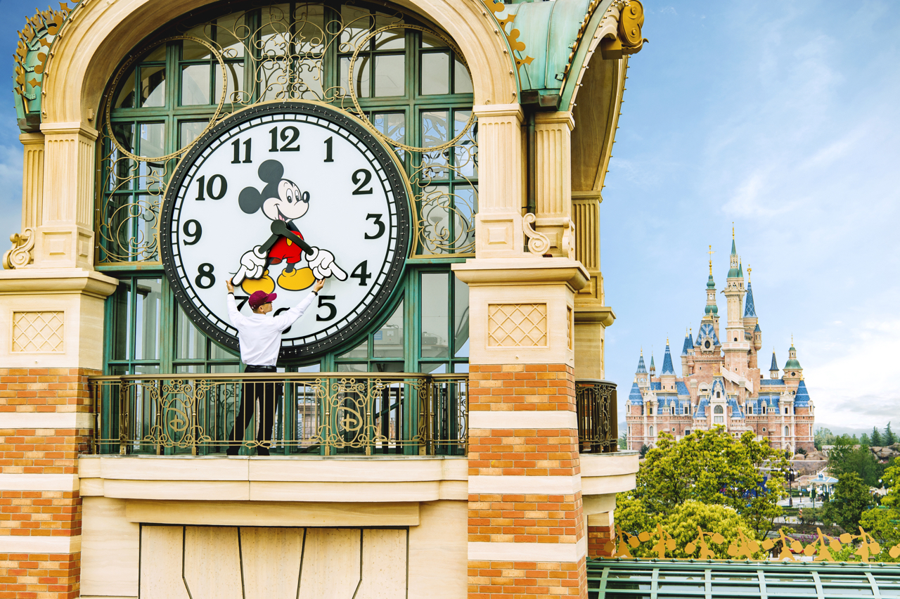 "ALMOST TIME - A Shanghai Disneyland cast member prepares the theme park's iconic ""Mickey Avenue"" clock in advance of the Grand Opening of Shanghai Disney Resort on June 16, 2016 with the spectacular backdrop of the world's largest Disney castle, The Enchanted Storybook Castle. Shanghai Disney Resort is a world-class family entertainment destination, imagined and created especially for the people of China. Ideal for multiple-day visits, the resort consists of Shanghai Disneyland, a theme park with magical experiences for guests of all ages; two richly themed hotels; Disneytown, an international shopping, dining and entertainment district; and Wishing Star Park, a recreational area with peaceful gardens and a glittering lake. The resort's hotels are the elegant, 420- room Shanghai Disneyland Hotel and the playful, 800-room Toy Story Hotel. Shanghai Disney Resort is a joint venture between The Walt Disney Company and Shanghai Shendi Group comprised of two owner companies (Shanghai International Theme Park Company Limited and Shanghai International Theme Park Associated Facilities Company Limited) and a management company (Shanghai International Theme Park and Resort Management Company Limited). (Matt Stroshane, photographer)"